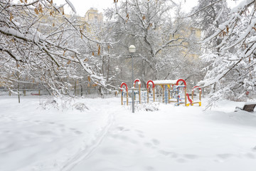 Winter landscape in Moscow, Russia. Scenery of snowy trees and playground. Panoramic scenic view of an empty urban park under snow.