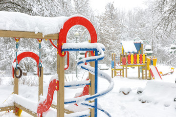 Winter in Moscow, Russia. Scenery of empty snowy colorful playground. Scenic view of urban kids park under snow.