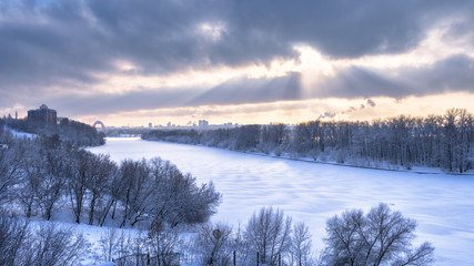 Winter landscape, Moscow, Russia. Scenery of frozen Moskva River covered ice and snow. Panoramic view of city under dramatic sky and sunlight.