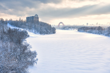 Winter landscape in Moscow, Russia. Scenery of Moskva River covered ice and snow in sunlight. Panoramic view of frozen river for background.