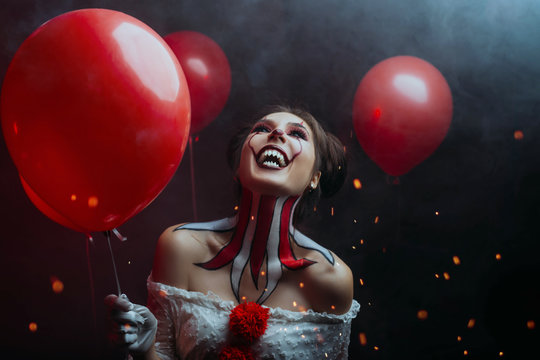 close-up portrait female clown woman scary crazy smiling laugh shows sharp teeth predator face, holding red balloons. backdrop dark gothic room sparks fire hell. art creative bright halloween make-up