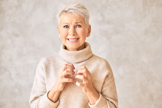 Negative human emotions, reactions and feelings. Stressed anxious middle aged woman in sweater grimacing feeling nervous going into panic. Depressed unhappy mature lady having frustrated look
