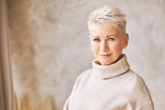 Horizontal shot of blonde fifty year old European female with stylish pixie haircut and blue eyes smiling at camera, having confident look posing isolated indoors. Aged people and maturity concept