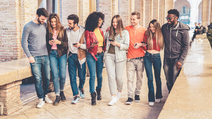 group of interracial friends meeting in the city center. they are having fun with smart phones and social media, walking together and chatting together.