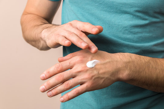 close up view of male hands moisturizing his hands with cream