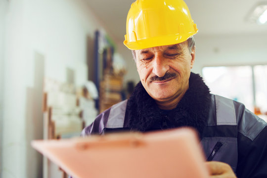 Portrait of caucasian senior man construction worker general laborer building contractor wearing yellow protective helmet holding pen and document checking data report project in the office warehouse