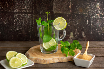 Empty glass teacup with fresh mint leaves and slices of lime on a wooden board.