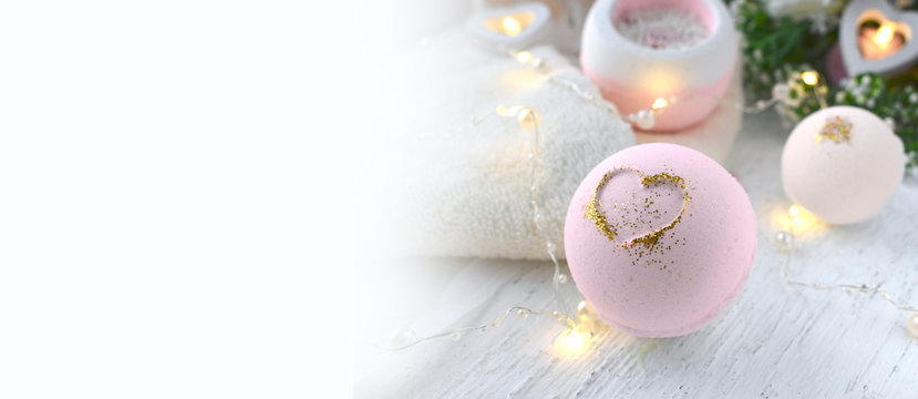 Mock up romantic spa composition. Pink bath bombs on lights background. Love or health lifestyle concept. Banner. Copyspace.