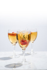 Strawberry Falling into Glass of White Wine with a Splash from the Front with Copy Space