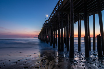 Ventura Pier at sunset, Ventura, California. Rocks and sand in foreground, water receded in low tide. Lamps on pier; colored twilight sky in background.