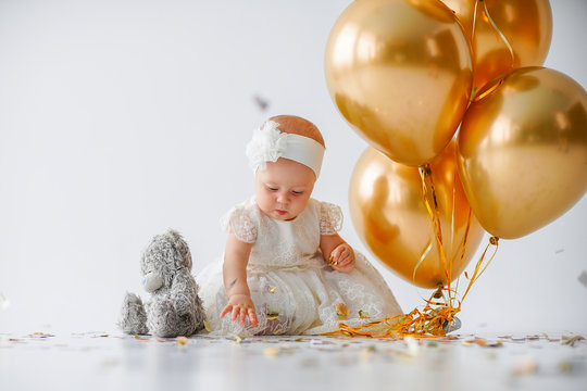 A one year old, baby girl sitting with a bunch of golden balloons and taddy bear on white background in studio.