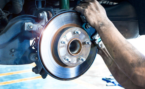 Close up car disk brake pad replacement service  with hand of mechanic man in car garage and copy space, use for disk brake service content
