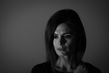 Black and white portrait of a middle age woman looking sad.