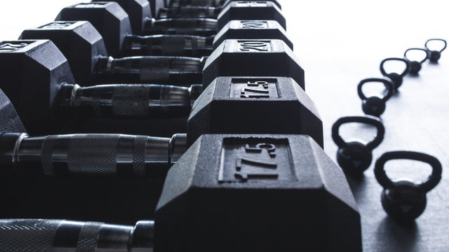 weights stacked neatly with kettle bells curving into the distance