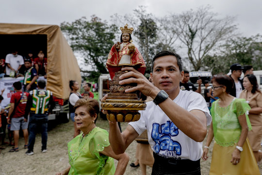 A man parades a statue of Baby Jesus while relief goods are distributed before a Catholic mass, at an evacuation center in Tagaytay City