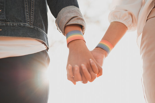 Cropped shot of young asian women LGBT lesbian couple holding hands with LGBT pride.
