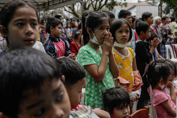 Children displaced by the erupting Taal Volcano attend a Catholic mass in an evacuation center, in Tagaytay City,