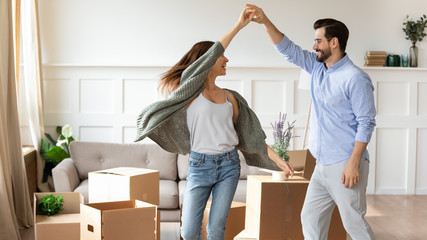 Overjoyed couple dance have fun on moving day