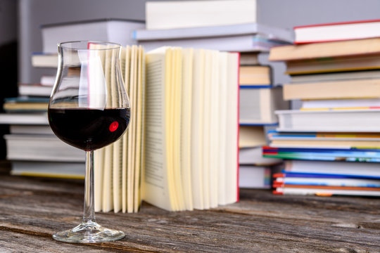 book and lwine glass in front of piles of different