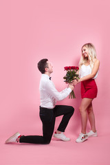 Man kneeling down and give flowers to pretty woman. Couple in love concept.