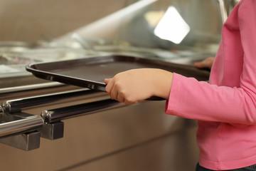 Little girl near serving line in canteen, closeup. School food