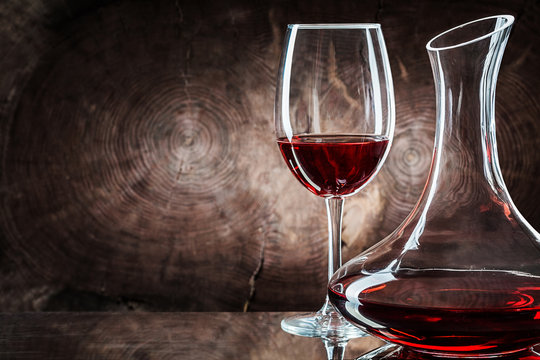 very close up decanter and wineglass with red wine on vintage wooden background