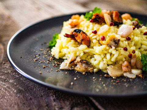 Risotto with seafood on wooden background