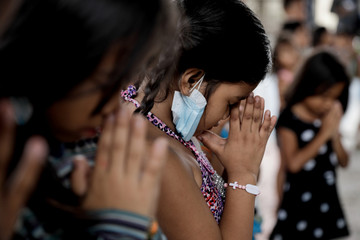 Children displaced by Taal Volcano's eruption pray solemnly during a Catholic mass in an evacuation center, in Tagaytay City