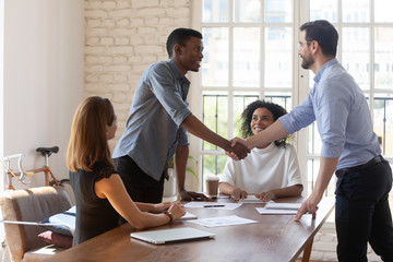Smiling diverse business partners shaking hands after signing contract