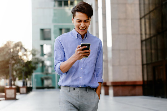 Portrait of a Happy Young Businessman Using Mobile Phone in the Urban City. Lifestyle of Modern People. Front View. Modern Building as background