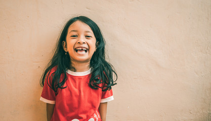 Portrait of an Asian little girl with long wavy hair and wearing a brick red shirt. Cute expression of 7 year old girl. Asian child.