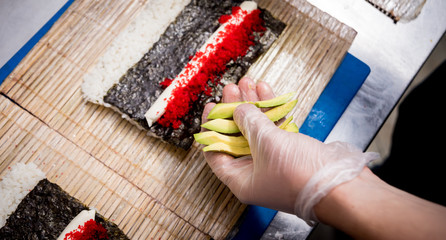 In de dag Sushi bar Process of making sushi and rolls at restaurant kitchen. Chefs hands with knife.