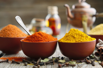 Aromatic spices and herbs - chili pepper, turmeric, curcuma, cardamom, cinnamon, cloves, anise, paprika, oil bottles and teapot on background. Ingredients for cooking and Ayurveda treatments. Papier Peint