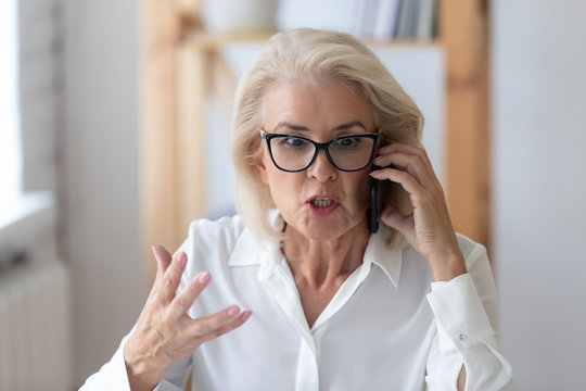 Mature businesswoman talking by phone arguing with client feels irritated