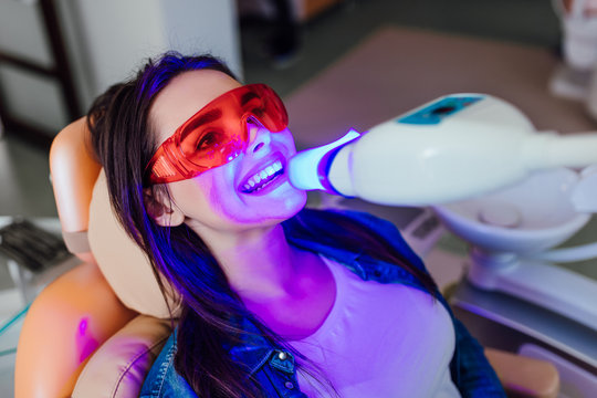 Teeth whitening for woman. Bleaching of the teeth at modern dentist clinic.