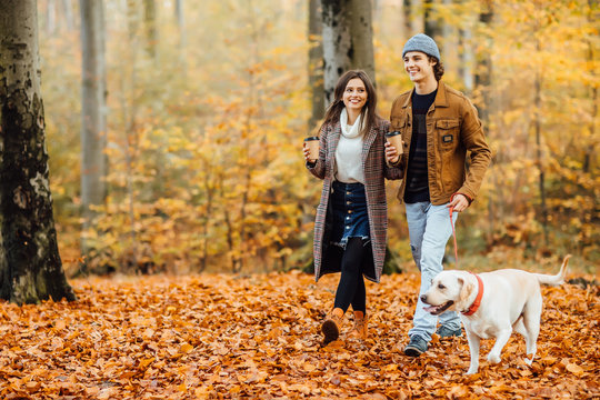 Family and hot autumn drink, couple in love holding cups of tea or coffee and holding hands, walking with dog.