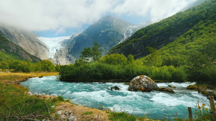 Wide lens shot: Briksdal glacier with a mountain river in the foreground. The amazing nature of Norway