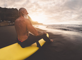 Happy fit senior man sitting on surfboard watching sunset time - Mature bearded surfer having fun on surfing day - Extreme sport and health people lifestyle concept