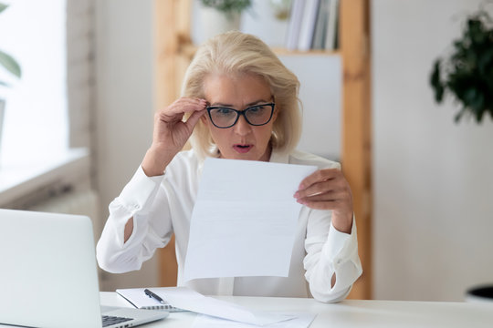 Middle-aged businesswoman lowered glasses reading letter feels shocked