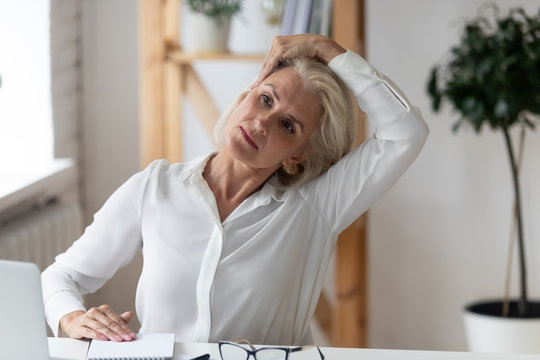 Middle-aged businesswoman seated at office workplace do gymnastics
