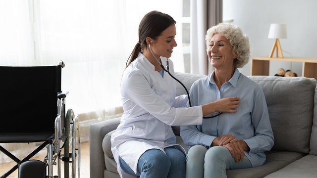 Friendly doctor listening to older woman lung or heart sound
