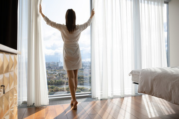 Rear view beautiful woman starting new day, opening curtains