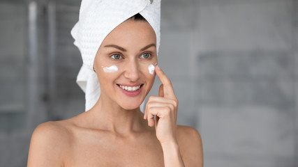 Head shot smiling beautiful woman with perfect skin applying cream
