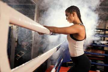 Poster Ontspanning exhausted after fight boxer woman in white top stand in ring, active and sportive female brunette in smoky ring. combate readiness and self-defense