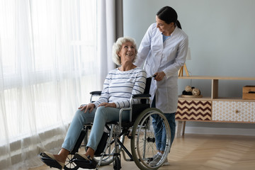Fototapete - Caregiver helping disabled older woman in wheelchair at home