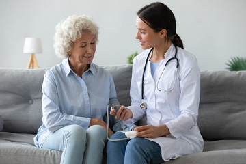 Friendly doctor checking older woman blood pressure at home
