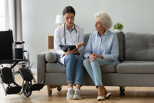 Doctor consulting disabled older woman, filling patient medical form