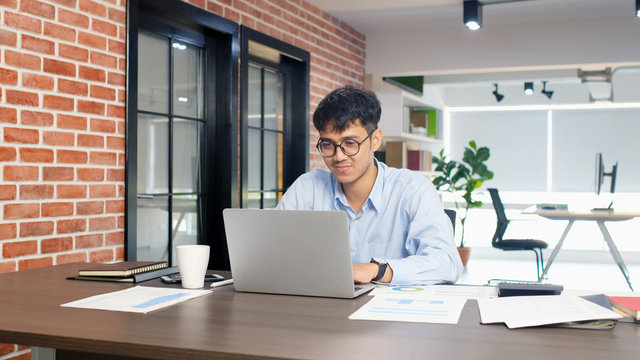 Young asian businessman concentrate on working with laptop computer at office, Asian office man comtemplate on working with laptop computer  business people and office lifestyle concept
