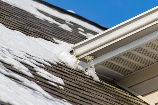 Melting snow on roof of house has formed ice on shingles and icicles hanging from gutter