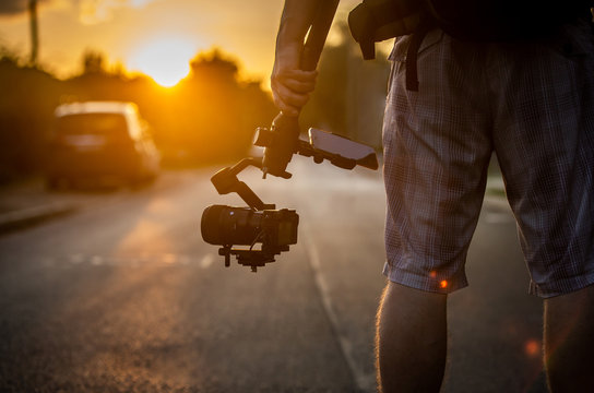 Man holding gimbal with sunset view.
